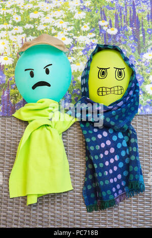 Two balloons with angry facial expression wearing green shawls - Stock Photo