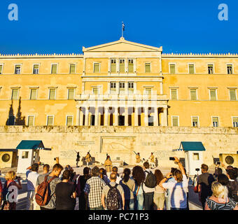 Tourists attending the change of the guard of the Evzones, soldiers of the Greek presidential guard,The Old Palace. Syntagma Square. Athens. - Stock Photo