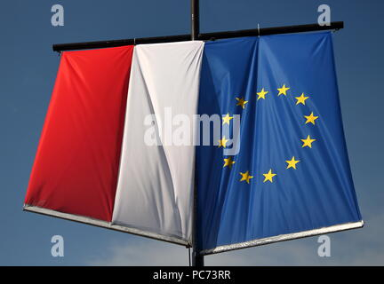 National flag of Poland and flag of European Union hang out together, next to each other, on pole, outdoor, in background blue sky - Stock Photo