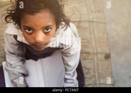 Village school girl portrait in school uniform. She is sitting on mat of her classroom floor holding school notebook in her lap for class assignments. - Stock Photo