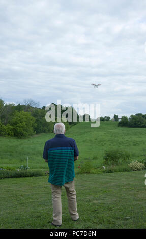 Man operating a dji Phantom Quadcopter Drone unmanned aerial vehicle in flight over open field. - Stock Photo