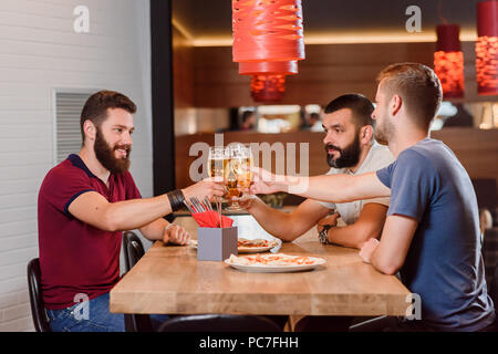 Group of male friends clinking glasses of tasty beer before drinking. Bearded men having appetizing pizza on their table. Three friends having fun and hanging out at pizzeria. - Stock Photo