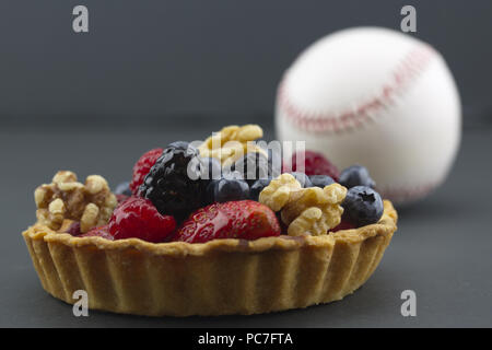 Healthy lifestyle choices reflected in fruits and nuts among food choices and activities like baseball.  Symbols placed on dark background. - Stock Photo