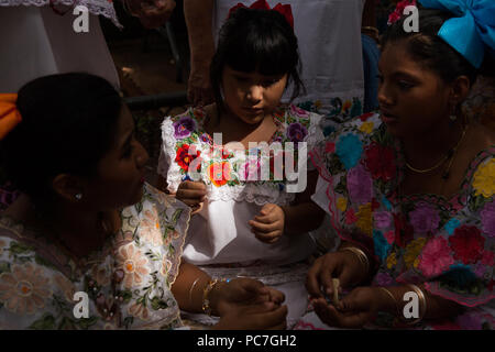 Mestizas preparing food and making tortillas at the altar contest of Hanal Pixan (day of the dead) in downtown Merida, Yucatan, Mexico. - Stock Photo