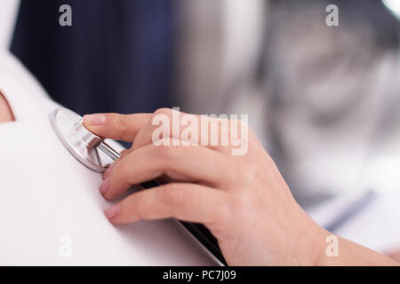 Close up shot of hand with stethoscope. Female doctor using stethoscope on patients chest listening to heart sounds. - Stock Photo