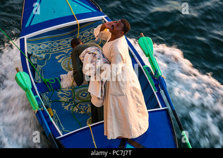 Local Egyptian men hawkers in small wooden boat tied to cruise ship selling linen products, River Nile, Egypt, Africa - Stock Photo
