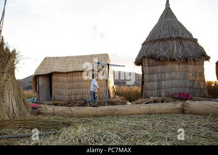 Small boy running around on Las Islas Flotantes (floating islands made of totora reeds). Lake Titicaca. Puno, Peru. Jun 2018 - Stock Photo