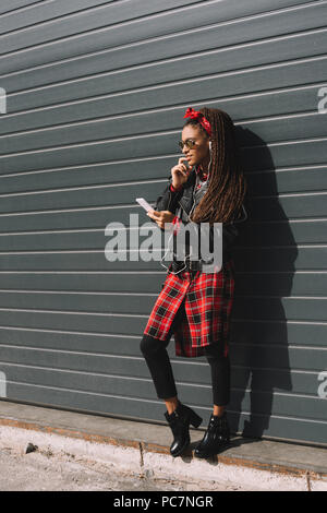 fashionable african american girl in sunglasses using smartphone - Stock Photo