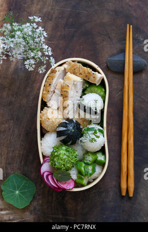 Bento box with onigiri, chicken and vegetables - Stock Photo