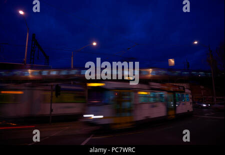 Two trams pass in opposite directions as a train passes on the bridge just overhead. - Stock Photo