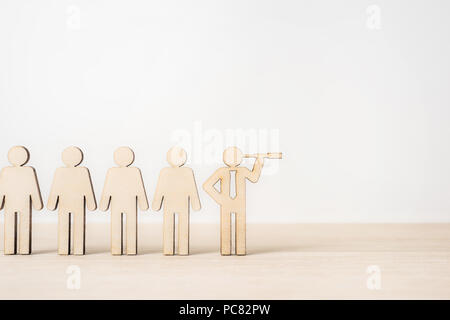 Business and design concept - group of wooden businessman icon with leadership concept on wooden desktop and white background - Stock Photo