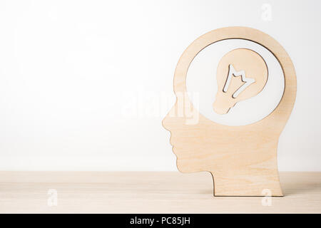 Business and design concept - wooden man silhouette head with light bulb on wooden desktop and white background - Stock Photo
