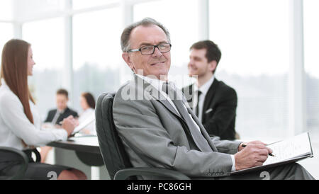 pensive mature businessman in suit with his team working behind - Stock Photo