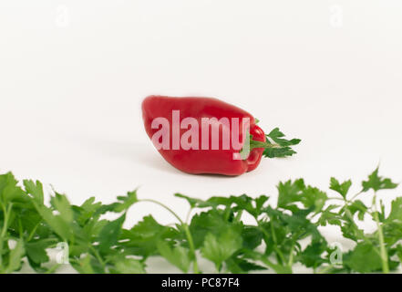 red bell pepper, and a sprig of parsley isolated on white background - Stock Photo