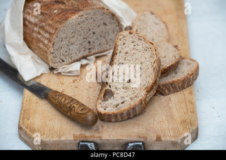 Sourdough bread with a vintage bread knife on a bread board. UK - Stock Photo
