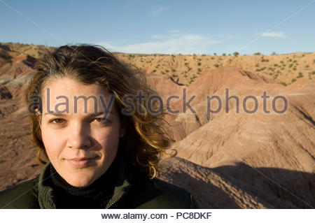 A woman stands atop a rock outcropping at a ranch. - Stock Photo