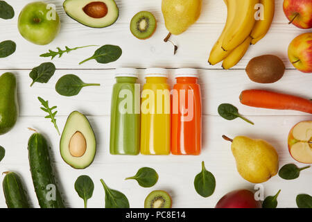 flat lay with bottles with detox smoothies in row with fruits and vegetables on wooden background - Stock Photo