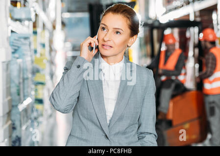 businesswoman talking on smartphone in shipping stock - Stock Photo