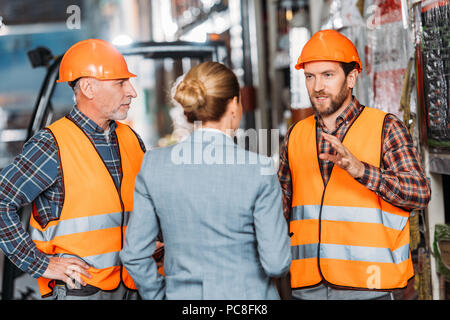 male workers in safety vests and helmets talking with inspector in storehouse - Stock Photo