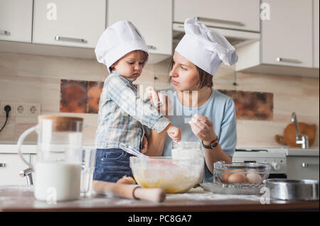 mother teaching her child how to prepare dough at kitchen - Stock Photo