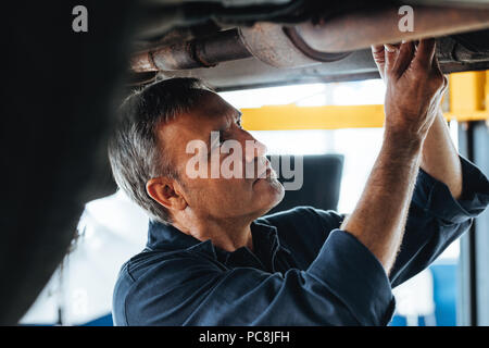Portrait of a mechanic at work in his garage. Mature auto technician working under a car service station. - Stock Photo
