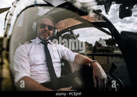 Portrait of mature male pilot with headset sitting in the private helicopter. Pilot sitting in the cockpit of a helicopter. - Stock Photo