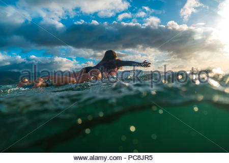 A woman surfing on the North Shore of Hawaii. - Stock Photo