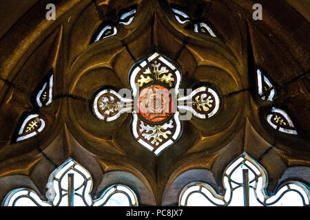A red rose decorative stained glass window in a sandstone frame at John Rylands Library, Manchester, UK - Stock Photo
