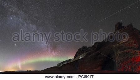 Low activity aurora in a dark starry sky with the Milky Way above basalt columns. - Stock Photo