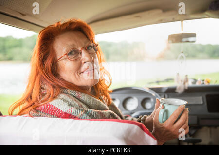 senior hipster woman in her van looking at camera - Stock Photo