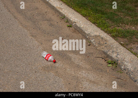 An empty discarded Coke bottle lying in the street or gutter in Speculator, NY USA, litter concept. - Stock Photo