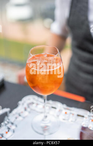 Aperol spritz cocktail in misted glass, selective focus. Alcoholic beverage based on bar counter with ice cubes and oranges. metal shakers in the background - Stock Photo