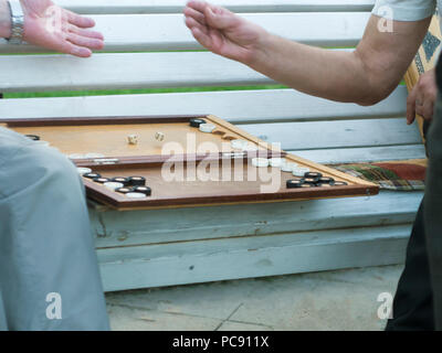 two senior men playing backgammon on the bench in the street close up - Stock Photo