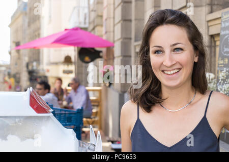 Saint-Malo, France - July 15th, 2018: A young woman working as waitress and serving soft ice cream outside a coffee store inside the walled city in Sa - Stock Photo