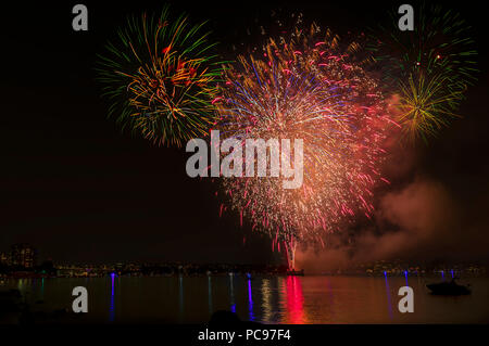 Multi Colored fireworks lights over the ocean in a big city, ancient bridge and modern buildings on the background, glowing and reflection of the ligh - Stock Photo