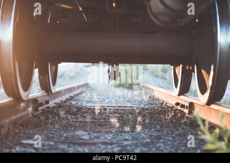 View under the train on wheels and rocky railway - Stock Photo