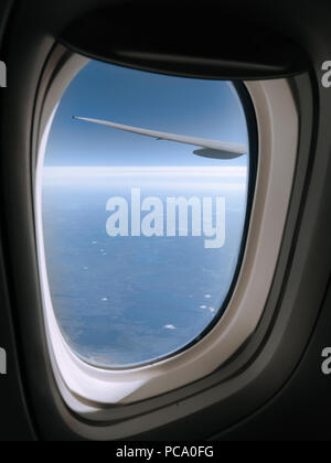 Beautiful view from a jet plane window high over Nunavut in Northern Canada. Window frame and airplane wing are seen in the foreground. - Stock Photo