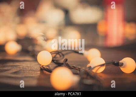 Selective focus decoration lamp light with on black wool and blurred background. Bulb warm light on black and shiny frieze fabric. Christmas day backg - Stock Photo