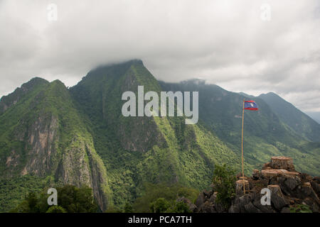 Viewpoint above Nong Khiaw in Laos PDR with Lao flag and misty lush green mountains in tbe back. - Stock Photo