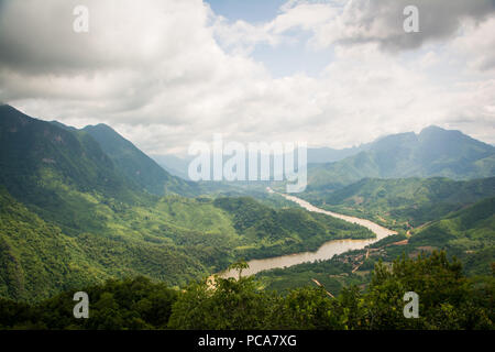 Nam Ou river flowing through beautiful lush green landscape seen from a viewpoint above Nong Khiaw in Laos PDR. - Stock Photo