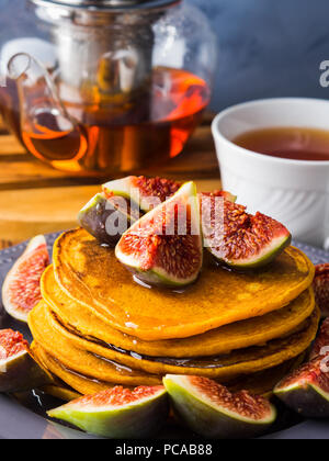 Stack of pumpkin pancakes with figs and honey and hot tea. Autumn food background on blue gray backdrop - Stock Photo