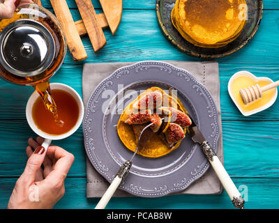 Eating pumpkin pancakes with figs and honey with hot tea. Autumn food background on green wooden table. Woman's hands - Stock Photo