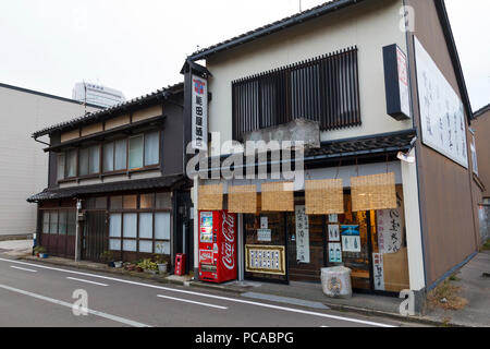 Traditional food store with coca-cola vending machine outdoors, in the city of Kanazawa in Japan - Stock Photo