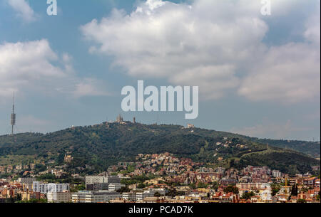View to the Tibidabo mountain with Sagrat Cor church and Amusement Park atop. The Torre de Collserola telecommunications tower is to the left. - Stock Photo