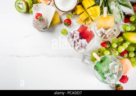 Tropical ice cream popsicles with chia seeds and fruit juices - pineapple, orange, mango, banana, kiwi, coconut, grapes, peach, strawberry, copy space - Stock Photo