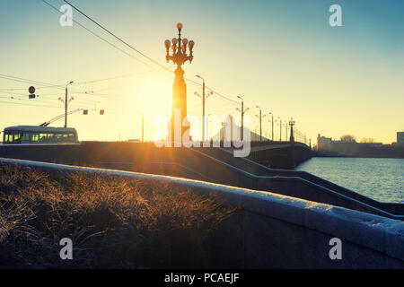 The sun's rays through the street lamp on the bridge across the Daugava River in Riga in December - Stock Photo