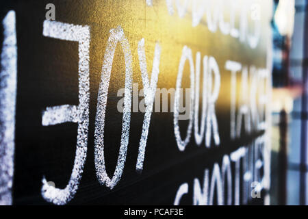 Blackboard with the word white chalk on a street in the glow of a golden sunset - Stock Photo