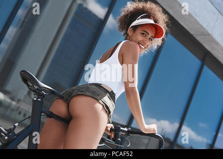 Young woman in visor free style on the street riding bicycle nea - Stock Photo
