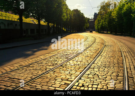Latvia, Riga. Evening sunlight on a bend of the street with the tram rails cobblestones near the park - Stock Photo