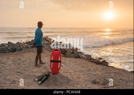 Lifeguard on duty seen from behind, looking over the ocean from a sunset beach. Red float and black flippers on the sand, waves crashing into rocks. - Stock Photo